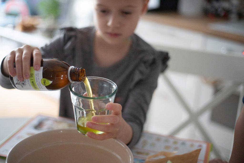 dziewczynka wlewa olej do szklanki