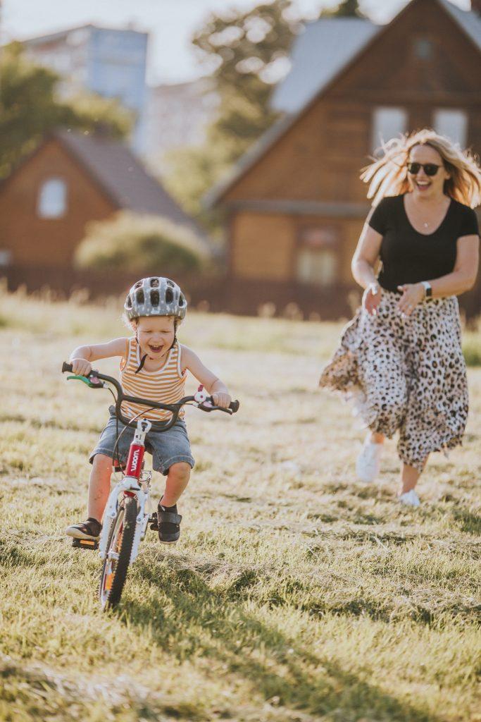 Jak nauczyć dziecko jeździć na rowerze - mama biegnie za rowerzystą