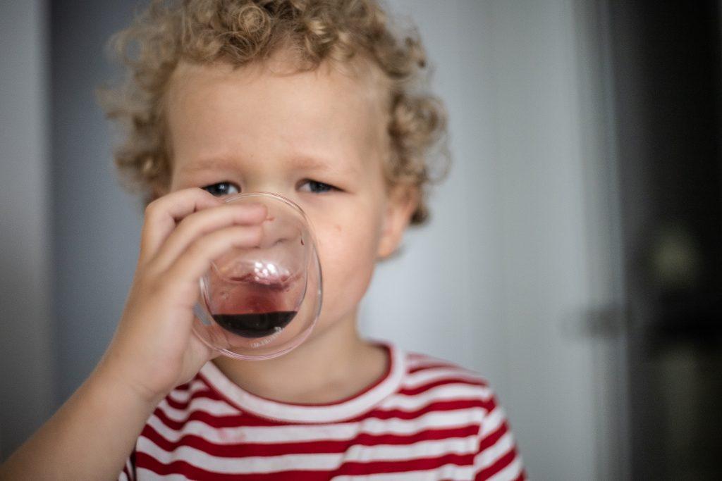 chłopiec pije sok z jagody kamczackiej