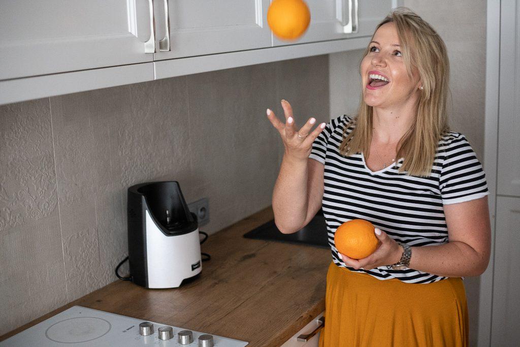 kobieta żongluje pomarańczami