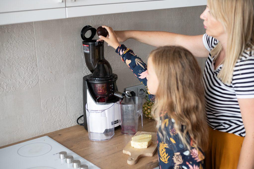 mama i córka wrzucają warzywa do wyciskarki wolnoobrotowej Kuvings