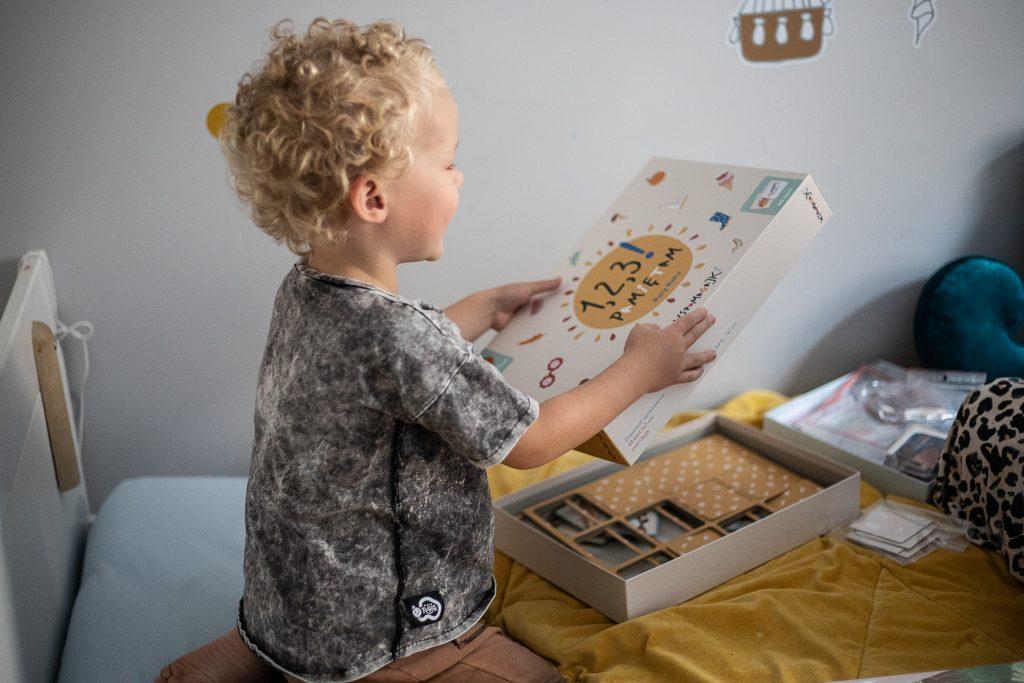chłopiec trzyma pudełko gry planszowej  -1,2,3 Pamiętam - pory roku