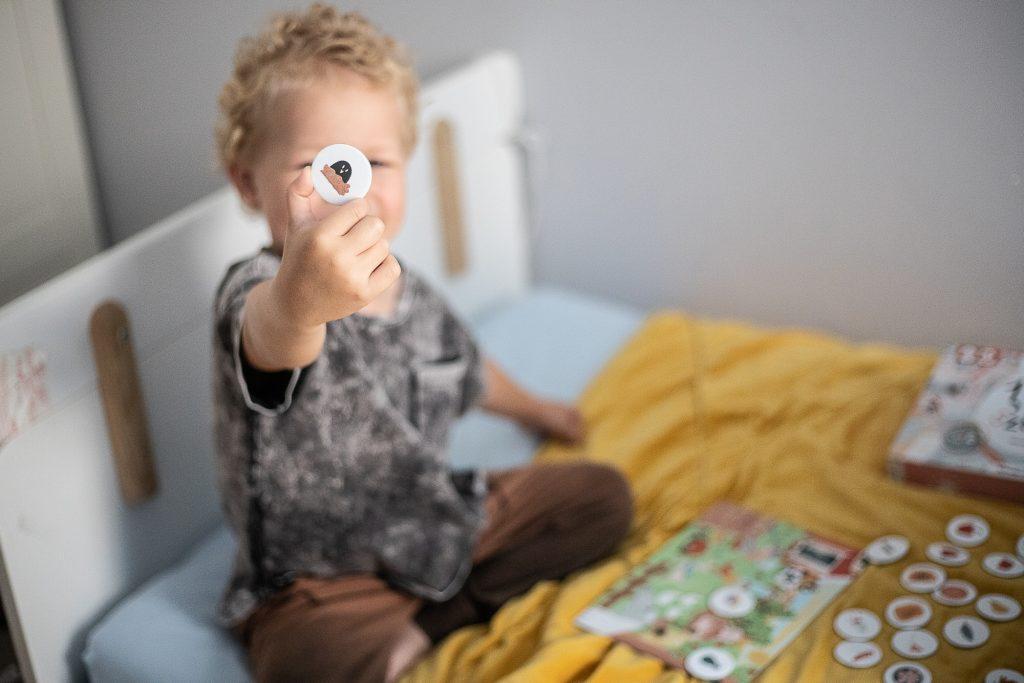 chłopiec pokazuje żeton z gry wspomagajki