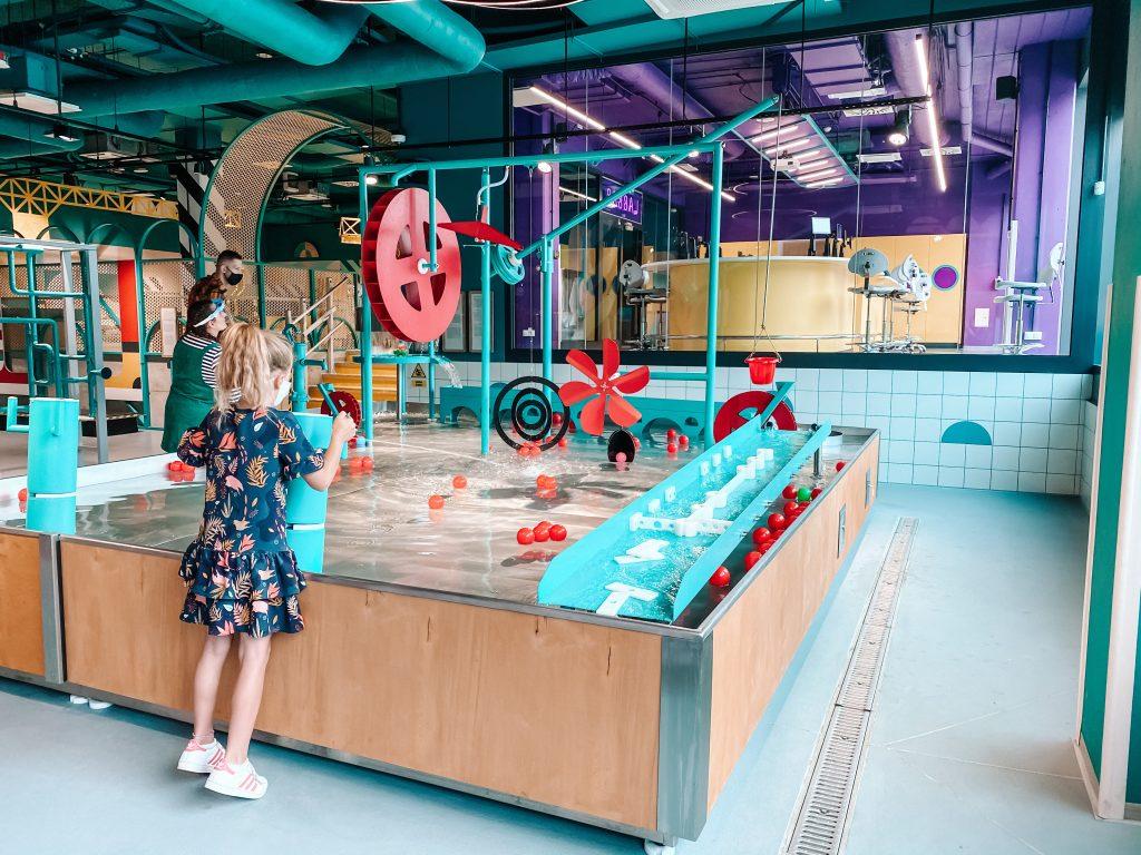 dziewczynka bawi się w strefie wodnej Epi-Centrum Nauki