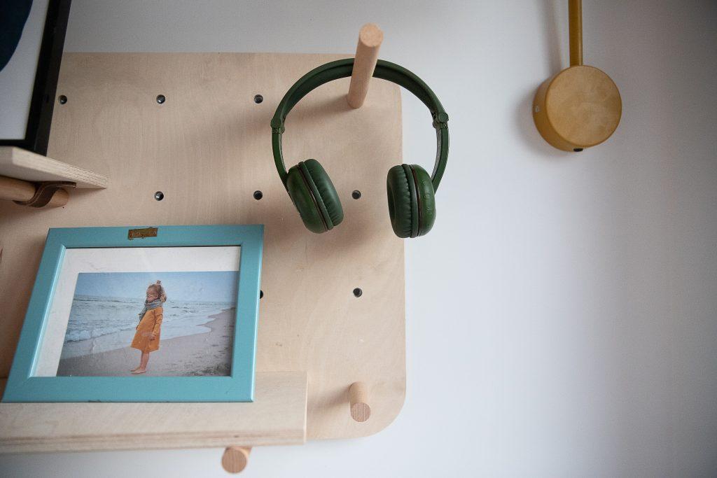 na zdjęciu wiszą zielone słuchawki Buddyphones