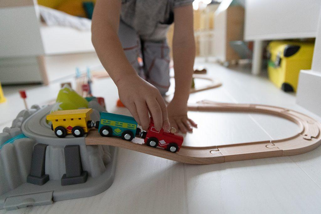 dziecko bawi się kolejką drewnianą